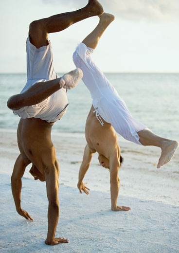 Two men turning cartwheels on beach : Stock Photo