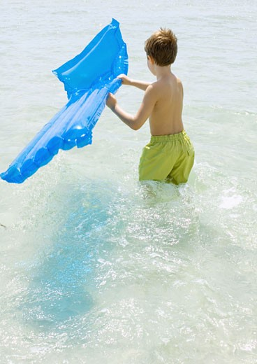 Boy carrying air mattress in sea : Stock Photo