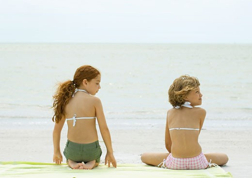 Two girls sitting on beach towel, rear view : Stock Photo