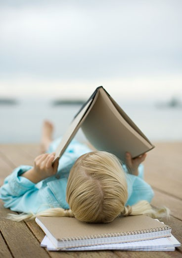 Girl reading book on dock : Stock Photo