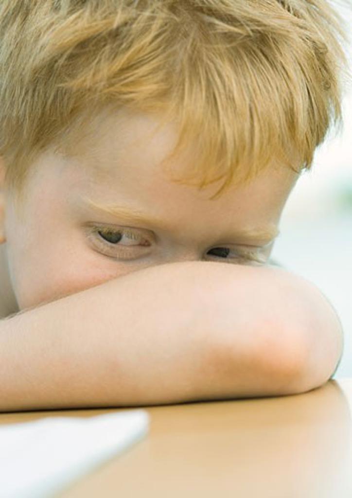 Boy resting head on arm : Stock Photo
