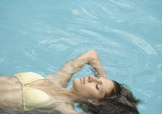 Stock Photo: 1569R-9015019 Woman floating on back in pool
