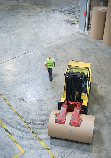 Stock Photo: 1569R-9015077 Fork lift picking up roll of paper