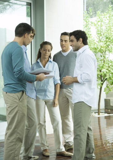 Group of casually dressed adults, standing together, discussing documents : Stock Photo