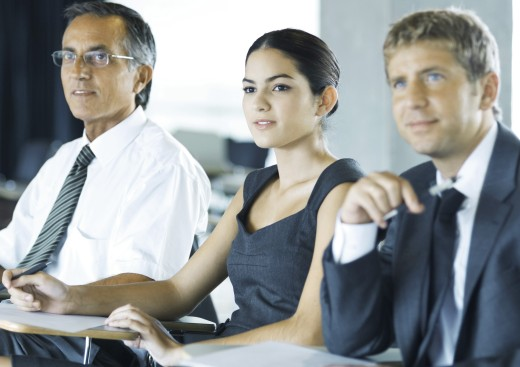 Stock Photo: 1569R-9015200 Businesspeople sitting holding, looking attentively out of frame