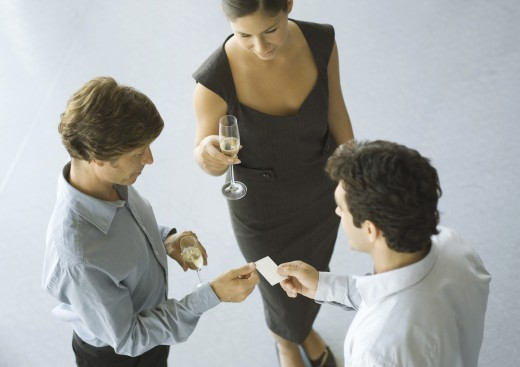 Executives exchanging business card during cocktail party : Stock Photo