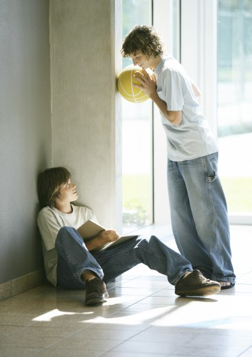 Stock Photo: 1569R-9015641 Boy sitting on floor studying, friend holding basketball, talking to him