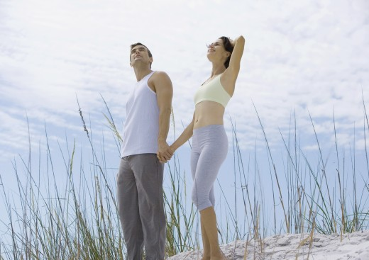 Couple standing holding hands in dunes : Stock Photo