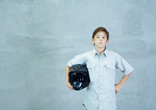 Boy standing with helmet under arm : Stock Photo