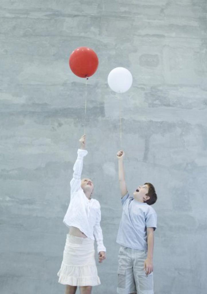 Two children holding helium balloons : Stock Photo