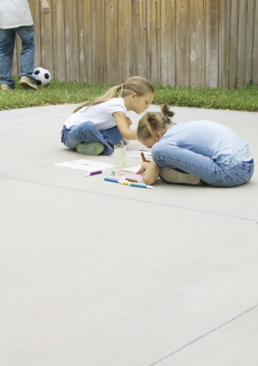 Kids sitting on driveway, drawing : Stock Photo