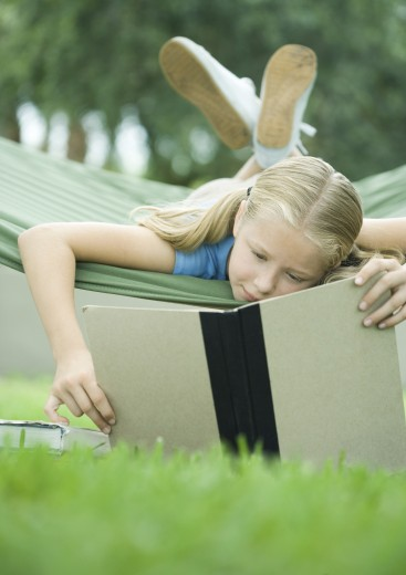Stock Photo: 1569R-9015963 Girl lying in hammock reading book