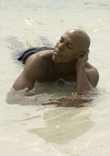 Man lying in shallow water, eyes closed : Stock Photo