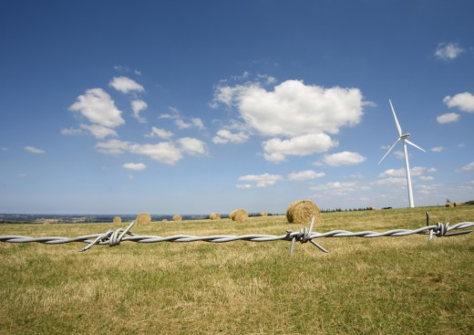 Wind turbine in field with bales of hay, barbed wire in foreground : Stock Photo