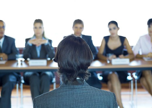 Executives sitting at conference table, looking at man in foreground : Stock Photo