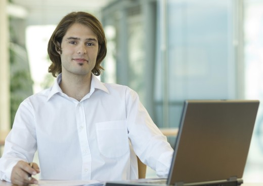Stock Photo: 1569R-9016475 Young businessman sitting at desk, smiling at camera