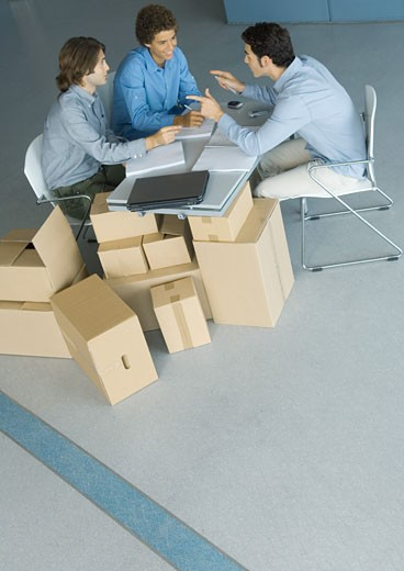 Businessmen sitting at table top supported by cardboard boxes, high angle view : Stock Photo