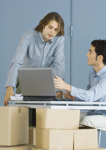 Businessmen using laptop, sitting at table top supported by cardboard boxes : Stock Photo