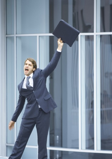 Stock Photo: 1569R-9016700 Businessman swinging briefcase and shouting