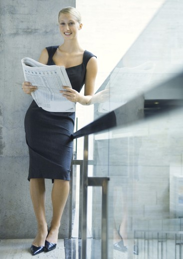 Stock Photo: 1569R-9016731 Businesswoman leaning against glass guard rail, reading newspaper, full length
