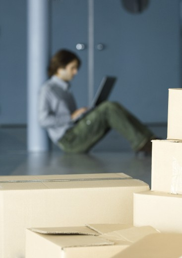 Stock Photo: 1569R-9016778 Young man sitting on floor using laptop, cardboard boxes in foreground