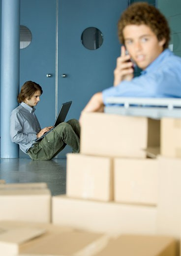 Young man sitting on floor using laptop, cardboard boxes in foreground : Stock Photo