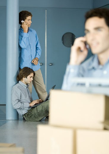Male colleagues using laptop and cell phone, cardboard boxes in foreground : Stock Photo