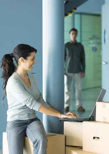 Stock Photo: 1569R-9016788 Woman sitting on cardboard box, using laptop, man standing in background