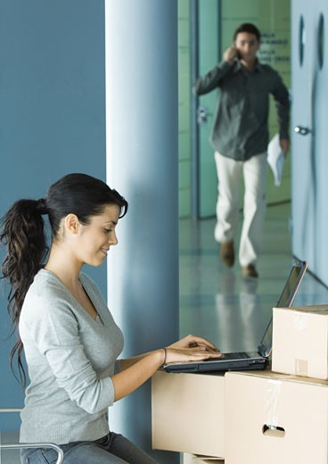 Stock Photo: 1569R-9016789 Woman sitting, using laptop on cardboard boxes, man approaching in background
