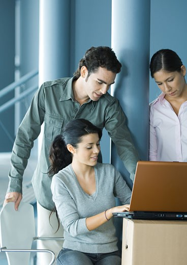 Woman sitting, using laptop on cardboard box, two colleagues looking over her shoulder : Stock Photo