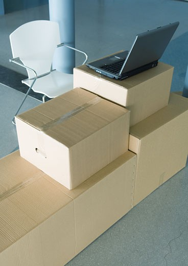 Stock Photo: 1569R-9016792 Open laptop on stack of cardboard boxes, and empty chair