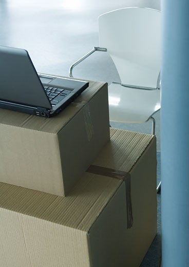 Stock Photo: 1569R-9016793 Open laptop on stack of cardboard boxes, and empty chair