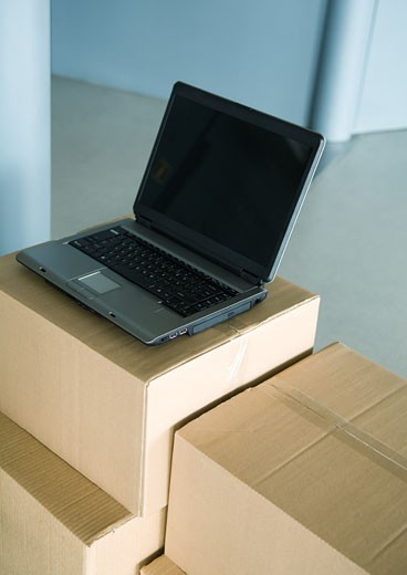 Open laptop on stack of cardboard boxes : Stock Photo