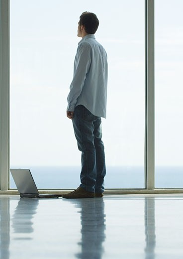 Stock Photo: 1569R-9016795 Man standing, looking out bay window, laptop on floor next to him