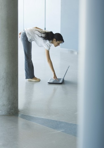 Young woman bending over, pressing key on laptop : Stock Photo