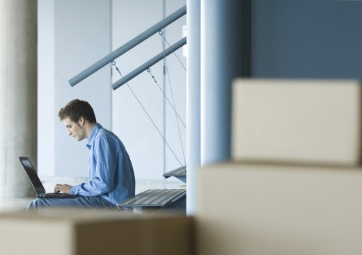 Man sitting on stairs using laptop, cardboard boxes in foreground : Stock Photo