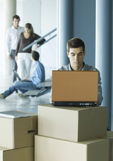 Man using laptop on stack of cardboard boxes, colleagues talking in background : Stock Photo