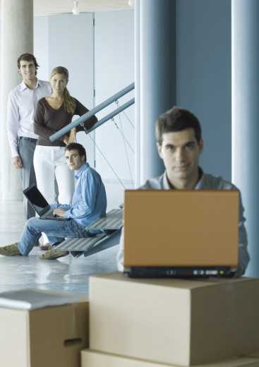 Man using laptop on stack of cardboard boxes, focus on colleagues standing in background : Stock Photo