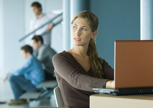Woman using laptop on cardboard box, colleagues in background : Stock Photo