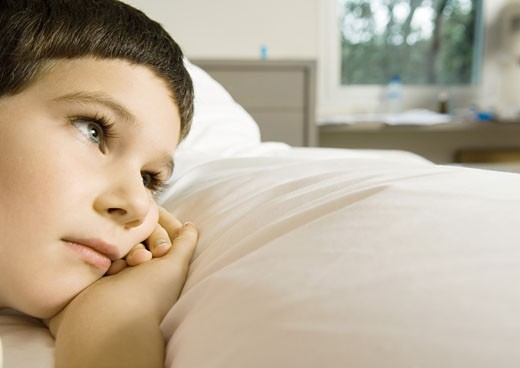 Child lying in bed, cropped view of head : Stock Photo