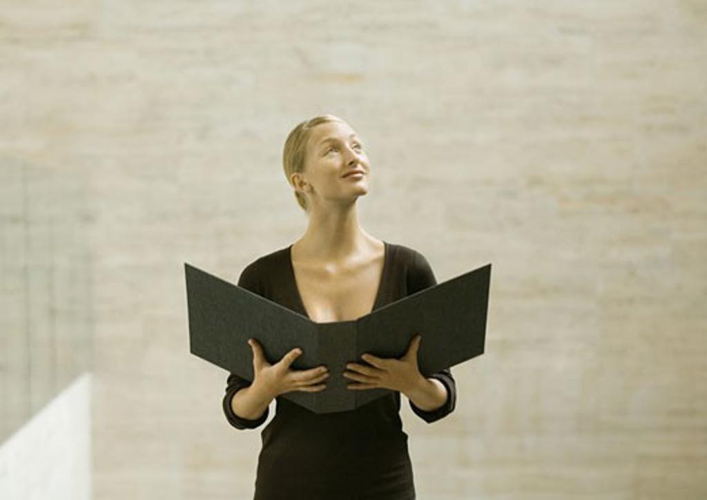 Woman standing holding open binder, looking away : Stock Photo