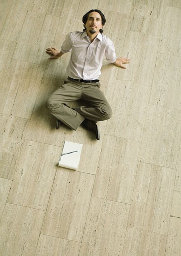 Man sitting on floor with pad of paper in front of him, leaning back, high angle view : Stock Photo