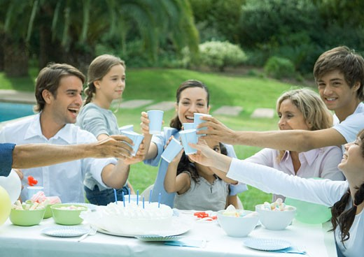 Family clinking cups over birthday cake : Stock Photo