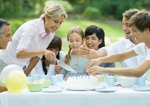 Stock Photo: 1569R-9017278 Outdoor birthday party, mature woman cutting birthday cake