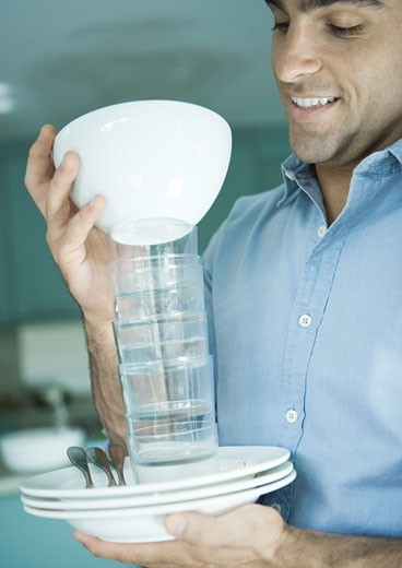 Man holding stack of dishes : Stock Photo
