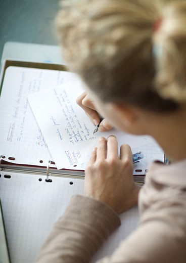 Preteen girl doing homework : Stock Photo