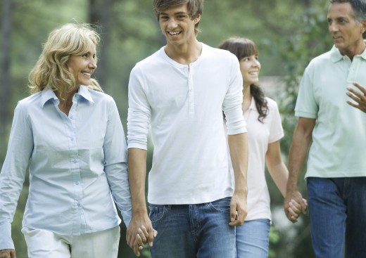 Mature couple walking, holding hands with teen grandchildren : Stock Photo