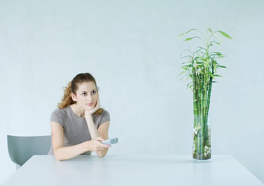 Woman sitting at table, pointing remote control : Stock Photo