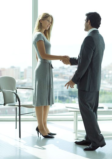 Stock Photo: 1569R-9017669 Businessman shaking hands with woman in lobby