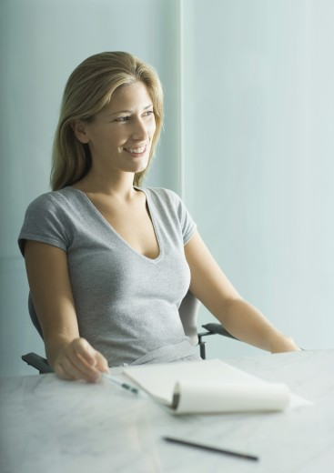 Woman sitting at table, notepad and pen on table : Stock Photo
